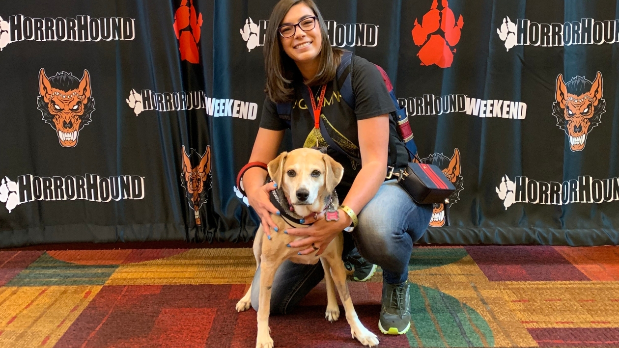Me and my service dog at a horror film convention. We are posing.