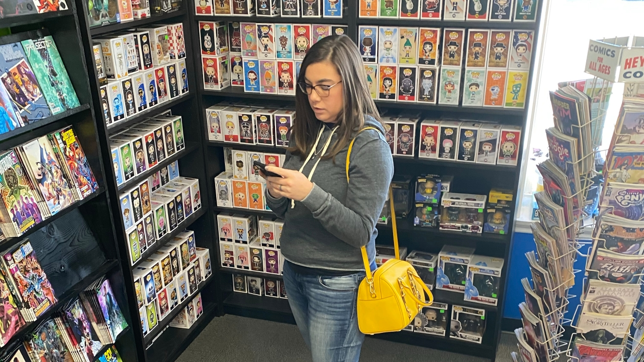 Image Description: An image of me looking at my phone while in a comic book store. In this image I am using the DC Universe app to alleviate my anxiety and help me select which comics I want to read. I am wearing a grey hoody, jeans, and black tennis shoes, a yellow purse is hanging on my shoulder.